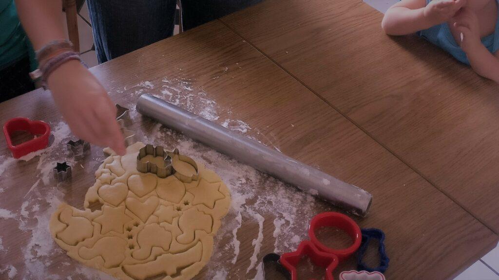 Ein brauner Küchentisch, auf dem ausgestochener Plätzchenteig liegt. Die Hand einer erwachsenen Person mit einer Keksform ist darüber zu sehen. Rechts sitzt ein Kleinkind am Tisch, dessen Hände zu sehen sind.