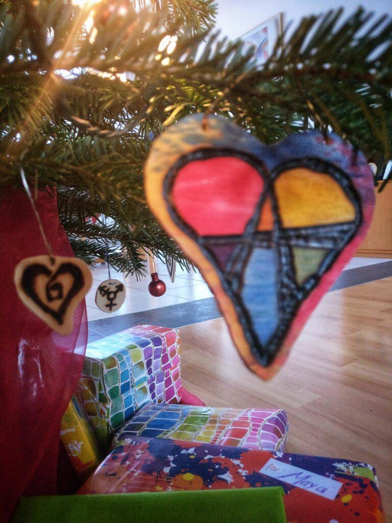 Ein Foto vom unteren Ende eines Weihnachtbaums. In der unteren Bildhälfte sind die darunter gelegten Geschenke zu sehen. In der oberen ist ein Tannenbaum-Zweig zu sehen, an dem drei auf Holz gebrannte Symbole hängen: im Vordergrund ein Anarchie-A inmitten eines Herzens, das für Beziehungsanarchie steht. Etwas weiter hinten ein Herz in dessen Mitte ein Quadrat abgebildet ist, was für Polyamorie steht. Ganz im Hintergrund ein kombiniertes astrologisches Mars-Venus-Anderes-Symbol, was für Trans steht.